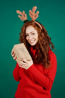 Porträt des glücklichen mädchens, das weihnachtsgeschenk am studioschuss hält