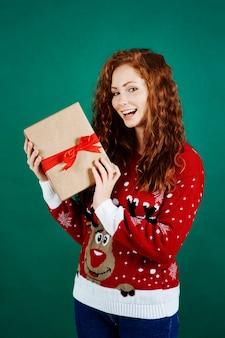 Porträt des glücklichen mädchens, das weihnachtsgeschenk hält