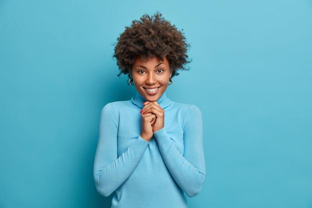 Porträt des glücklichen mädchens hat afro-haar hält hände unter kinn sieht mit erfreut zufriedenem ausdruck aus