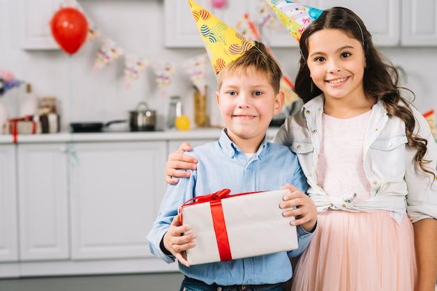 Porträt des glücklichen mädchens mit dem jungen, der geburtstagsgeschenk hält