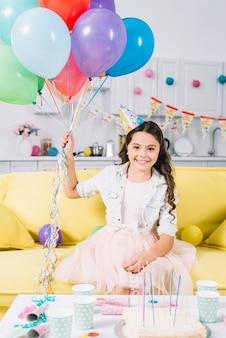 Porträt des glücklichen mädchens sitzend auf dem sofa, das bunte ballone hält
