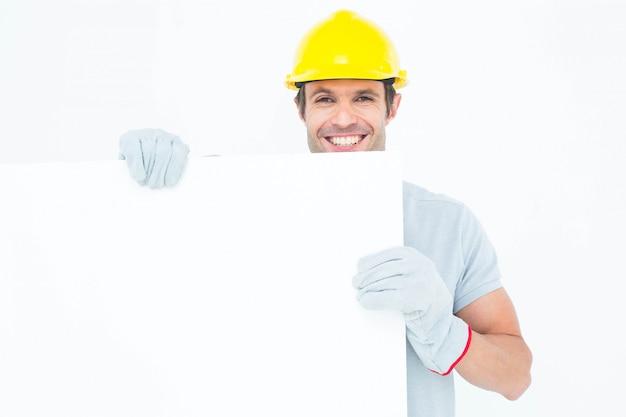 Porträt des glücklichen männlichen architekten mit anschlagbrett über weißem hintergrund