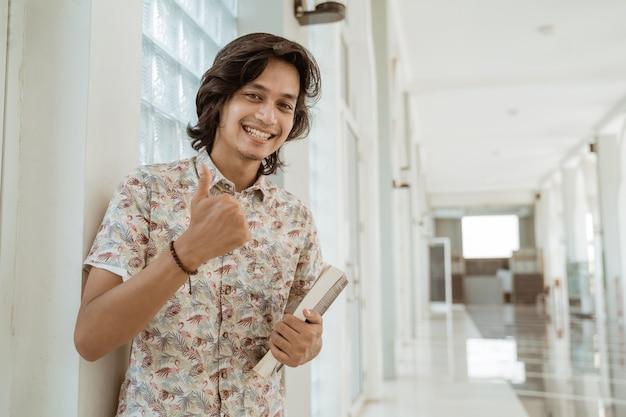 Porträt des glücklichen männlichen studenten, der buch hält und daumen zeigt kamera auf dem campus betrachtet.