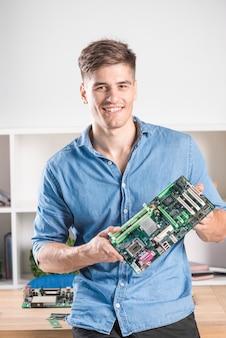 Porträt des glücklichen männlichen technikers, der modernes computermotherboard hält