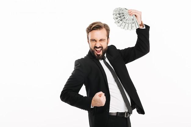 Porträt des glücklichen männlichen unternehmers, der seinen preis freut und fan des geldes 100-dollar-scheine hält, lokalisiert über weißer wand
