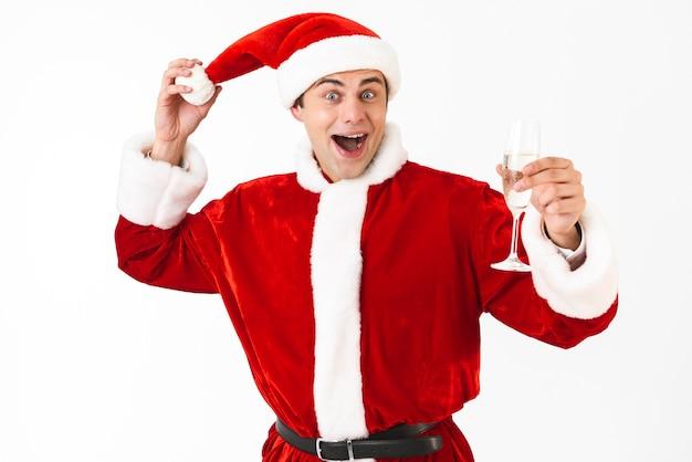 Porträt des glücklichen mannes 30s im weihnachtsmannkostüm und im roten hut, der champagner vom glas trinkt
