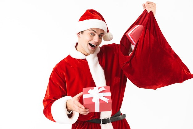 Porträt des glücklichen mannes 30s im weihnachtsmannkostüm und im roten hut, der festliche tasche mit geschenkboxen hält