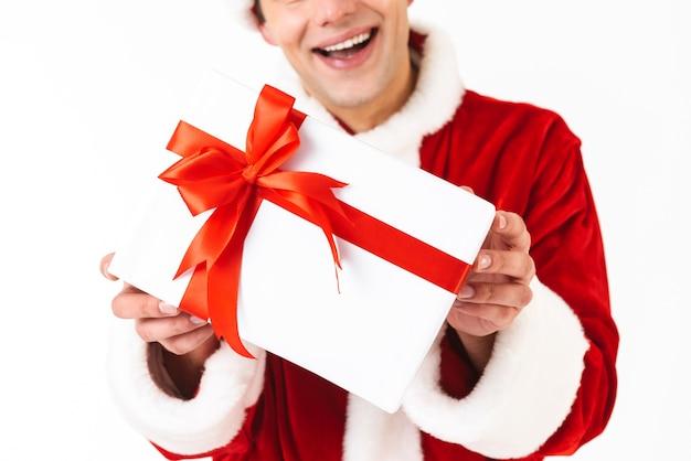 Porträt des glücklichen mannes 30s im weihnachtsmannkostüm und im roten hut, der geschenkbox hält