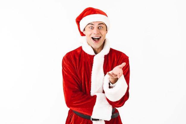 Porträt des glücklichen mannes 30s im weihnachtsmannkostüm und im roten hut, der zur kamera gestikuliert