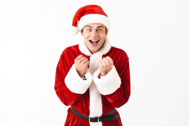 Porträt des glücklichen mannes 30s im weihnachtsmannkostüm und im roten hut, die mit lächeln sich freuen