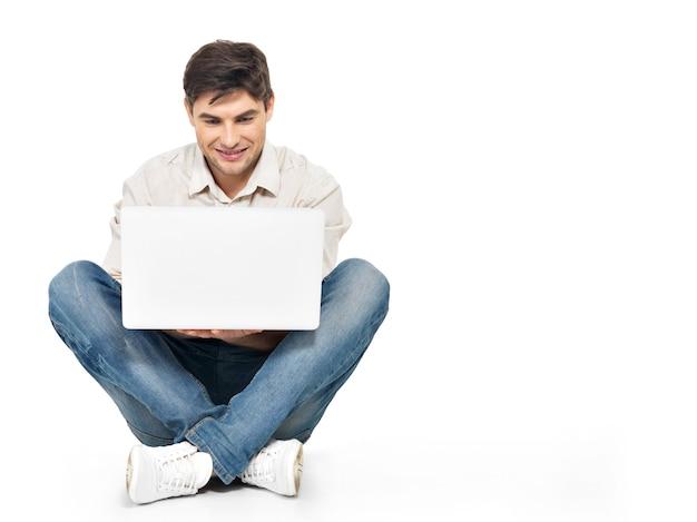 Porträt des glücklichen mannes, der am laptop arbeitet, der im bildschirm lokalisiert auf weiß sucht.