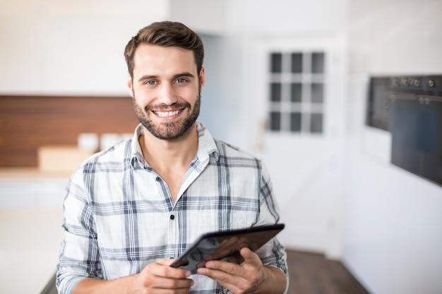 Porträt des glücklichen mannes, der digitale tablette verwendet