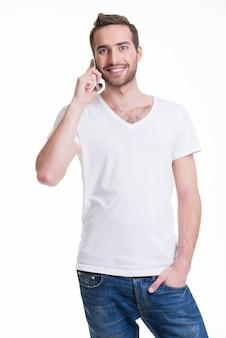Porträt des glücklichen mannes, der per handy in casuals anruft - isoliert auf weiß