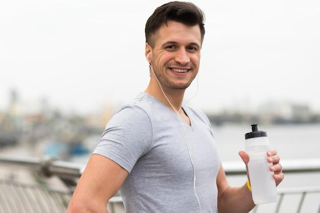 Porträt des glücklichen mannes, der wasserflasche hält