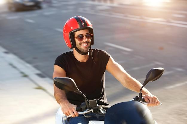 Porträt des glücklichen mannes mit sturzhelm und sonnenbrille auf motorradfahrt