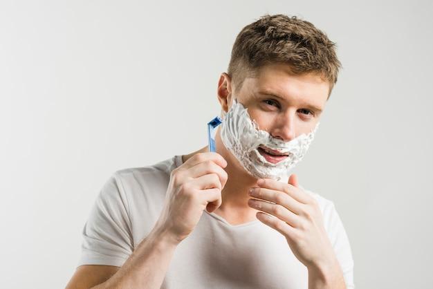 Porträt des glücklichen mannes schauend auf kamera und sein gesicht mit dem rasiermesser lokalisiert über grauem hintergrund rasierend