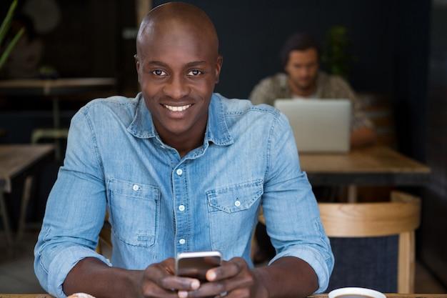 Porträt des glücklichen mannes unter verwendung der digitalen tablette am holztisch im kaffeehaus