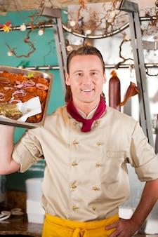 Porträt des glücklichen metzgers mit geschmackvollem lebensmittel diente auf behälter an seinem shop