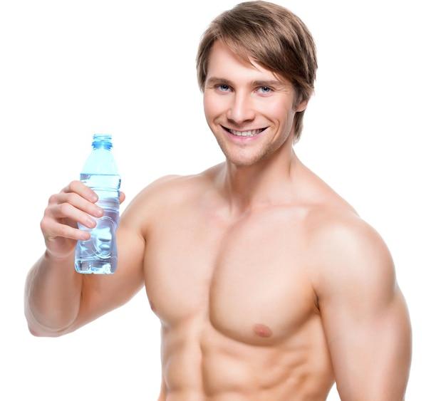 Porträt des glücklichen muskulösen hemdlosen sportlers hält wasser
