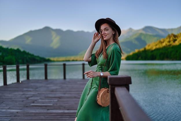 Porträt des glücklichen netten lächelnden attraktiven reisendenmädchens, das hut und grünes kleid trägt, das allein auf pier mit see- und bergblick steht. genießen sie eine ruhige, friedliche atmosphäre in der natur
