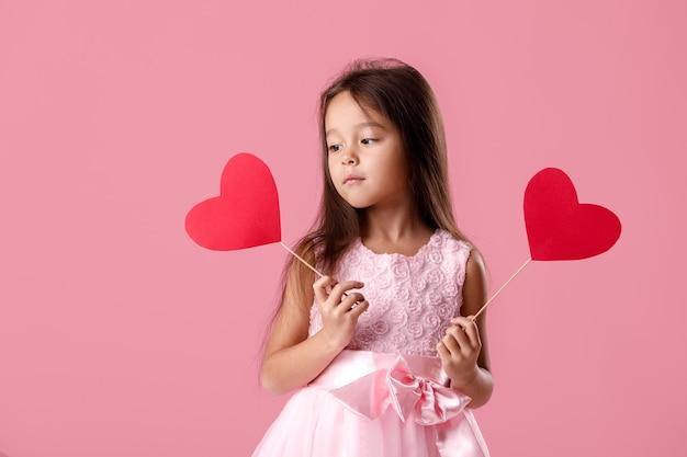 Porträt des glücklichen niedlichen kleinen kindermädchens in einem rosa kleid, das papierherz hält