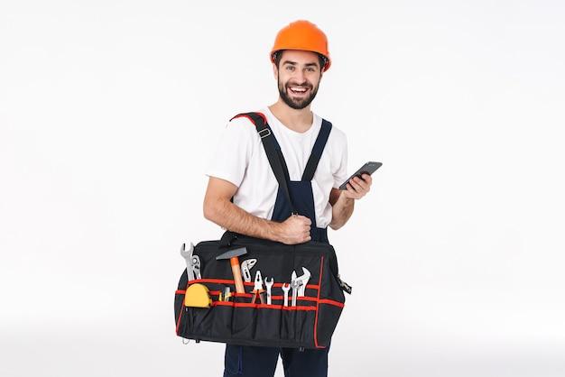 Porträt des glücklichen optimistischen erbauers des jungen mannes im helm lokalisiert über der weißen wand, die tasche mit ausrüstungsinstrumenten unter verwendung des handys hält.