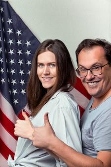 Porträt des glücklichen paares auf dem hintergrund der us-flagge