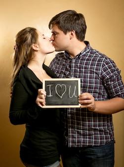 Porträt des glücklichen paares, das brett mit liebeserklärung küsst und hält