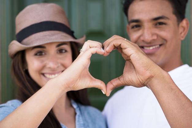 Porträt des glücklichen paares, das herzformzeichen mit den händen macht. glückliches erwachsenes paar, das sich verliebt, das herzformsymbol mit den händen macht. romantisches liebespaar, das herzzeichen mit den händen macht