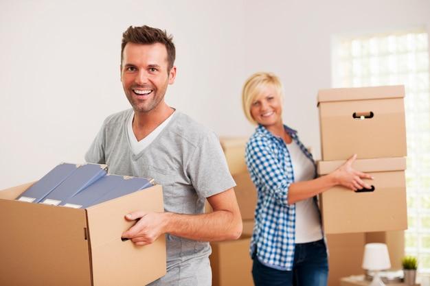 Porträt des glücklichen paares, das pappkartons im neuen zuhause trägt