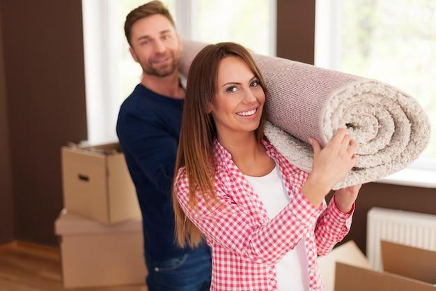 Porträt des glücklichen paares, das teppich für neues zuhause trägt