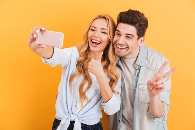Porträt des glücklichen paares mann und frau, die selfie-foto auf handy machen, während mit fingern gestikulierend