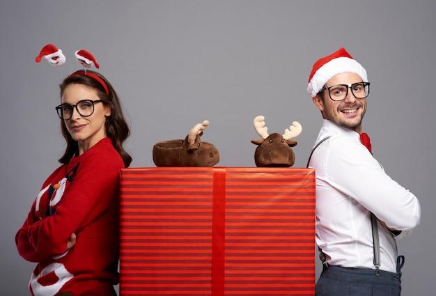 Porträt des glücklichen paares mit großem weihnachtsgeschenk