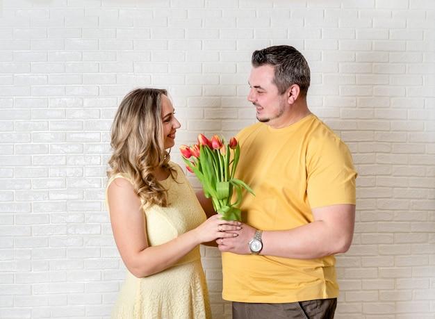 Porträt des glücklichen paars, des ehemanns und der frau mit frühlingsblumenblumenstrauß