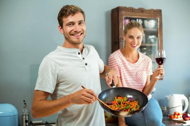 Porträt des glücklichen paars lebensmittel kochend