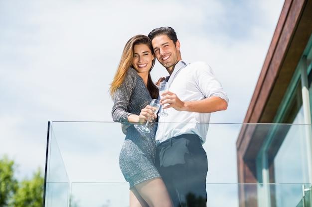Porträt des glücklichen paars mit champagner am balkon