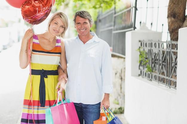 Porträt des glücklichen paars mit einkaufstaschen und ballonen