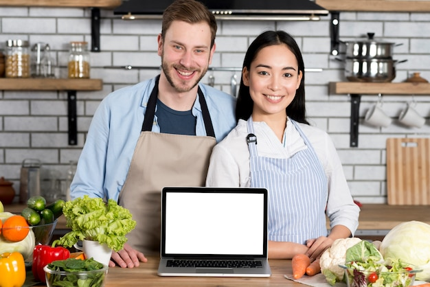 Porträt des glücklichen paars mit laptop des leeren bildschirms auf hölzerner küchenarbeitsplatte