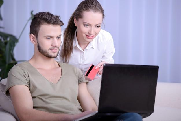 Porträt des glücklichen paars online kaufend mit kreditkarte.