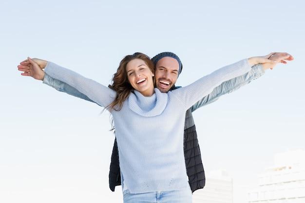 Porträt des glücklichen paars stehend mit den armen ausgestreckt
