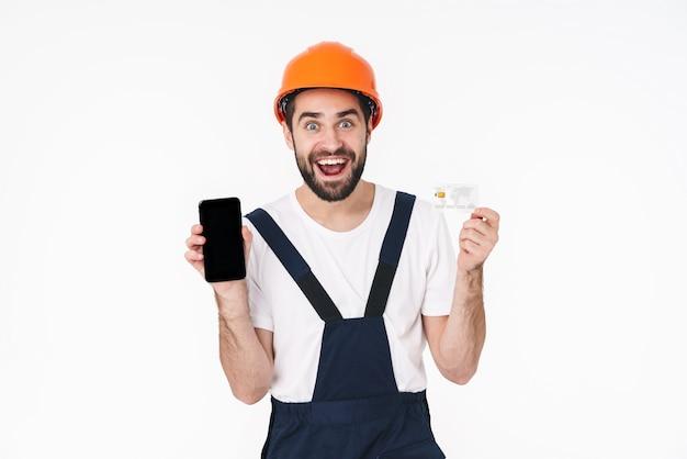 Porträt des glücklichen positiven erbauers des jungen mannes im helm lokalisiert über der weißen wand, die kreditkarte hält, die anzeige des handys zeigt.