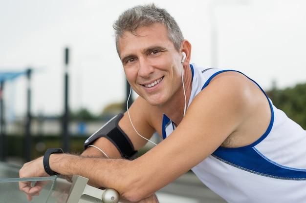 Porträt des glücklichen reifen mannes, der musik auf kopfhörern genießt