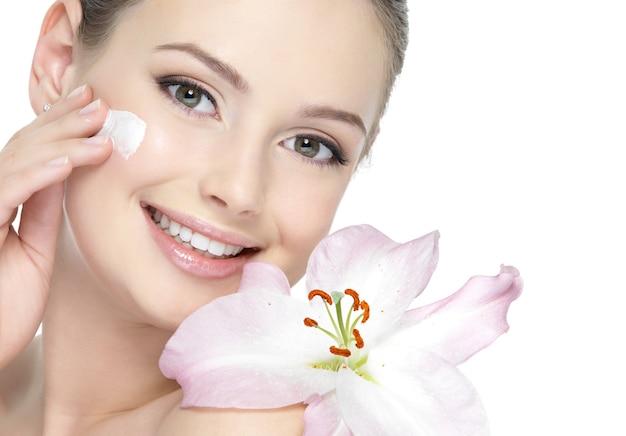 Porträt des glücklichen schönen mädchens mit lilie, die creme aufträgt