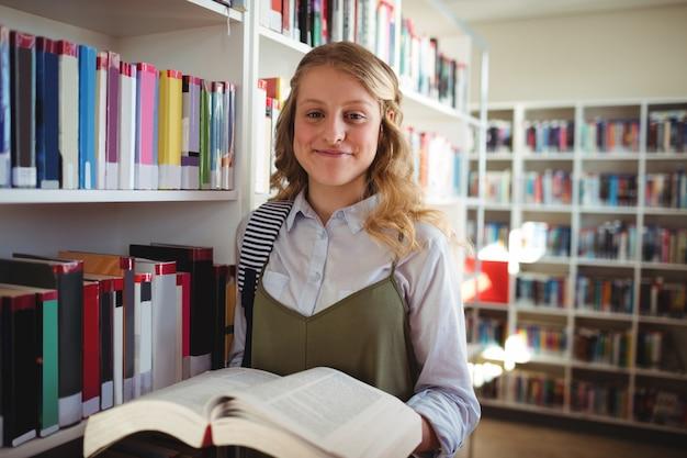 Porträt des glücklichen schulmädchens, das buch in der bibliothek hält
