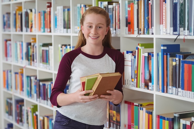 Porträt des glücklichen schulmädchens, das bücher in der bibliothek hält
