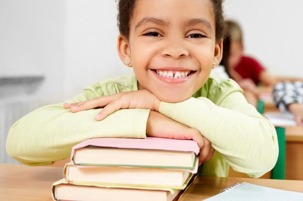 Porträt des glücklichen schulmädchens im klassenzimmer der grundschule.