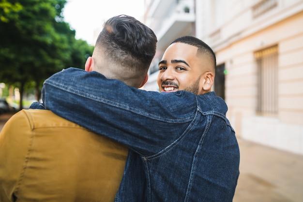 Porträt des glücklichen schwulen paares, das zeit zusammen verbringt und auf der straße umarmt. lgbt und liebeskonzept.