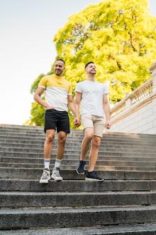 Porträt des glücklichen schwulen paares, das zeit zusammen verbringt und hände beim gehen auf der straße hält. lgbt und liebeskonzept.