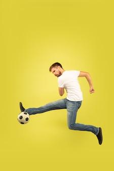 Porträt des glücklichen springenden mannes in voller länge lokalisiert auf gelb