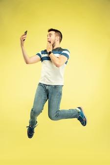 Porträt des glücklichen springenden mannes mit gadgets auf gelber wand